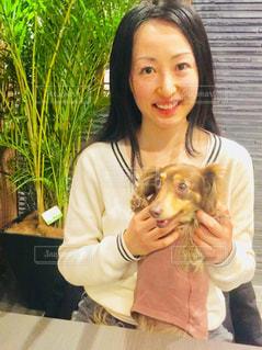カメラにポーズ犬を持つ女性の写真・画像素材[1089502]