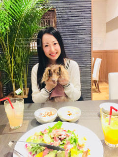 食品のプレートをテーブルに座っている女性の写真・画像素材[1089510]