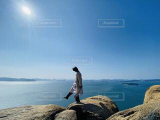 岩の丘を歩く女性の写真・画像素材[4614493]