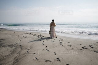 浜辺を歩くワンピースを着た女性の写真・画像素材[4637652]