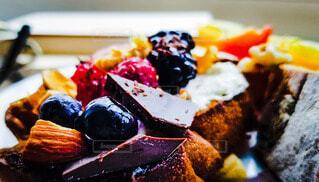 バゲットの上にのったフルーツとミックスナッツとチョコレートのクローズアップ vividの写真・画像素材[4697563]