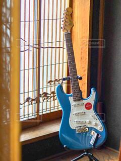 窓の横にあるギターの写真・画像素材[4653337]
