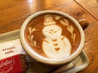 コーヒーの隣に座っているスープのボウルの写真・画像素材[2804268]