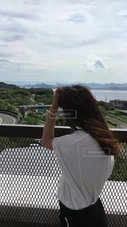 フェンスの前に立っている女性の写真・画像素材[726229]