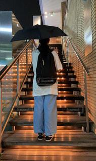 黒い傘とリュックを背負って佇む女の子の写真・画像素材[4772940]