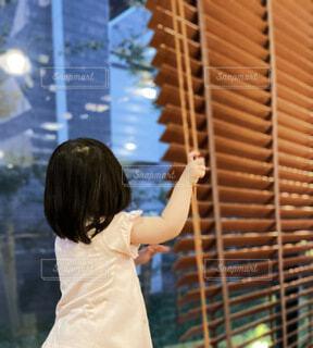 外が気になりブラインドを上げる子供の写真・画像素材[4713447]