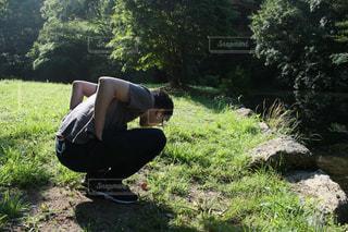 草の中に立っている男の人の写真・画像素材[1220600]