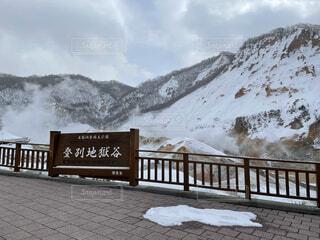 フェンスの隣にある雪に覆われた公園のベンチの眺めの写真・画像素材[4761891]