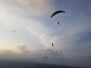 曇りの日に凧を飛ばす人々のグループの写真・画像素材[4755706]