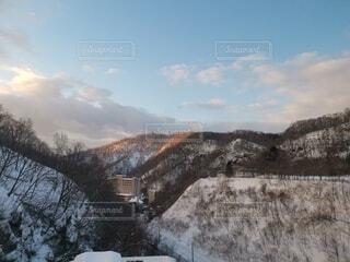 雪に覆われた山をスキーに乗っている男の写真・画像素材[4751406]
