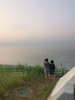 夕暮れの海を見る女性の写真・画像素材[4751409]