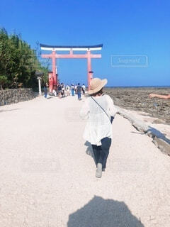砂浜を歩く麦わら帽子を被った女の人の写真・画像素材[4754023]