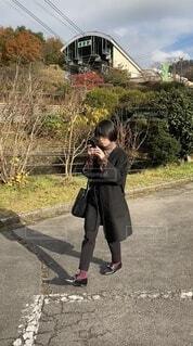 スマホを見ながら歩く女性の写真・画像素材[4803161]