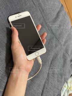 ベッドで横になりながら携帯充電する姿の写真・画像素材[4759868]