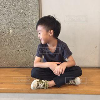 ベンチに座っている少年の写真・画像素材[708283]