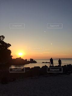 ビーチでの背景の夕日に人々 のグループの写真・画像素材[761710]