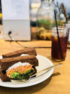サンドイッチとワインのガラスをのせた白プレートの写真・画像素材[1635999]