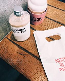 テーブルの上のコーヒー カップの横に牛乳瓶の写真・画像素材[1636003]