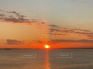 沈む夕日と飛行機の写真・画像素材[4763104]