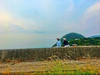 堤防に腰かけて笑いあう二人の後ろ姿の写真・画像素材[4823578]