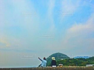 堤防に腰掛けている女子二人の後ろ姿の写真・画像素材[4823577]