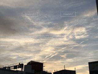 都市に沈む夕日と飛行機雲の写真・画像素材[4778766]