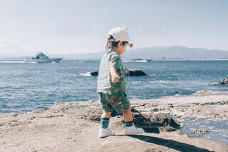 浜辺に立っている陽気な男の子の写真・画像素材[4830521]