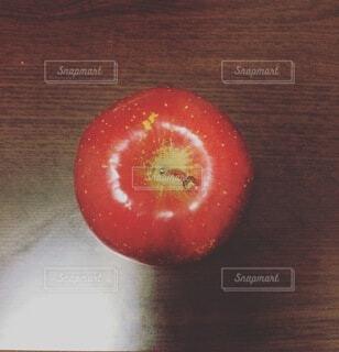 机の上に置いてある上から見た赤いリンゴの写真・画像素材[4769734]