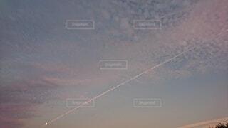 月と飛行機雲が重なった夕方の空の写真・画像素材[4791078]
