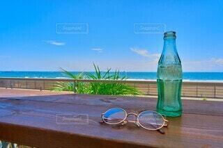 海辺のテーブルでボトルとサングラスの写真・画像素材[4780450]