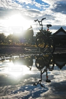 水たまりに反射する自転車と日光の写真・画像素材[4784414]