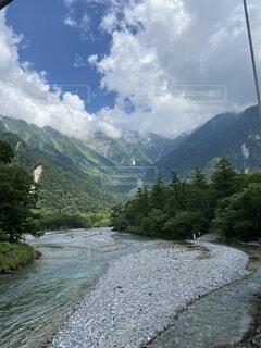 山の側に木がある道の写真・画像素材[4826423]
