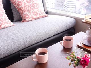 一杯のコーヒーとテーブルの上の花の花瓶の写真・画像素材[926781]