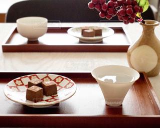 テーブルの上の花の花瓶をのせた白プレートの写真・画像素材[980753]