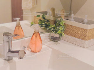 テーブルの上の花の花瓶の横に座っている白いシンクの写真・画像素材[1516146]