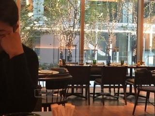 窓の前のテーブルに座っている人の写真・画像素材[1700277]