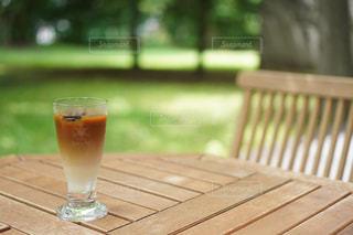 木製のベンチの上に座っているワインのグラスの写真・画像素材[2307515]
