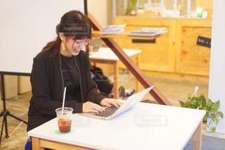 ラップトップコンピュータを使ってテーブルに座っている女性の写真・画像素材[2513736]