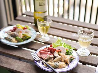 食べ物の皿を持ったテーブルに座っている人の写真・画像素材[3326486]