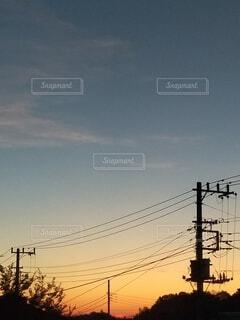 日没時に通りを横断する電車の写真・画像素材[4900297]