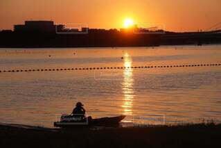 水の体に沈む夕日の写真・画像素材[4877084]