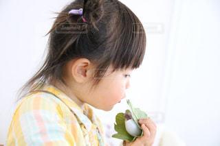 食べ物を食べている小さな女の子の写真・画像素材[2199865]