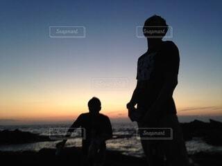 夕暮れの海辺で佇む男性の写真・画像素材[4871606]