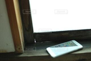 窓枠に置いた携帯電話の写真・画像素材[4889278]