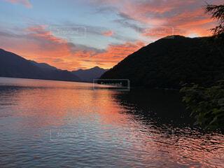 山を背景にした水の体に沈む夕日の写真・画像素材[4876086]