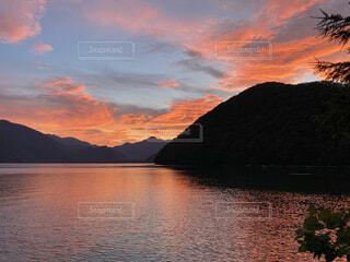 山を背景にした水の体に沈む夕日の写真・画像素材[4876085]