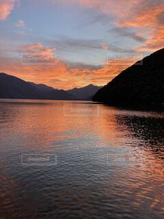 山を背景にした水の体に沈む夕日の写真・画像素材[4876081]