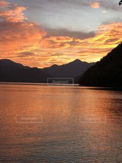 山を背景にした水の体に沈む夕日の写真・画像素材[4876095]