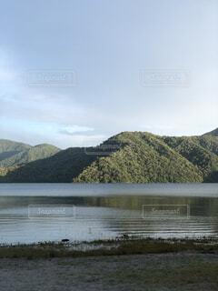 背景に山のある水の体の写真・画像素材[4876096]