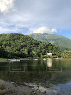 背景に山のある水の体の写真・画像素材[4876097]